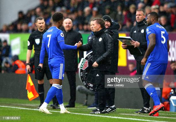 Demarai Gray of Leicester City shakes hands with Brendan Rodgers Manager of Leicester City after he is subbed for Wes Morgan of Leicester City during...