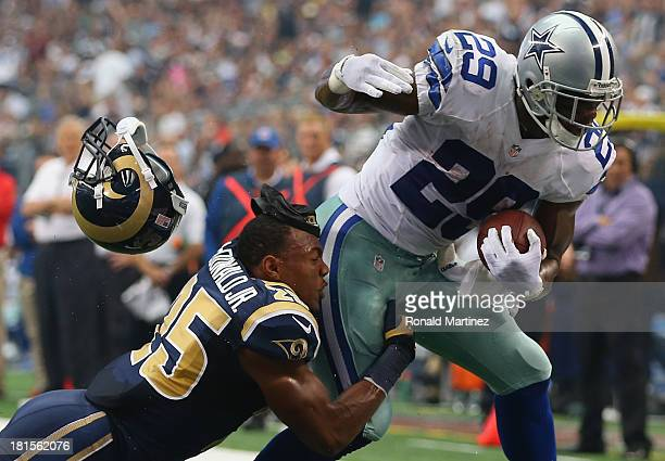 DeMarco Murray of the Dallas Cowboys scores a touchdown while tackled by T.J. McDonald of the St. Louis Rams at AT&T Stadium on September 22, 2013 in...