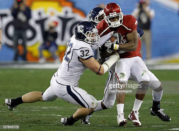 DeMarco Murray of the Oklahoma Sooners runs the ball as Scott Lutrus of the Connecticut Huskies attempts to take it away in the first half during the...