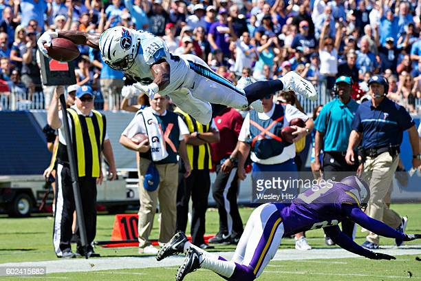 DeMarco Murray of the Tennessee Titans dives over Terence Newman of the Minnesota Vikings into the end zone for a touchdown during the first half of...