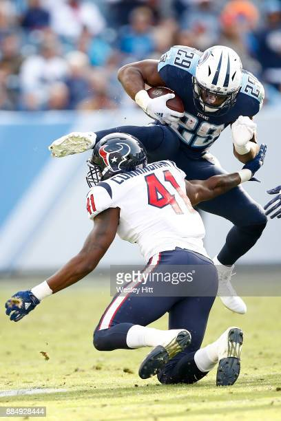 DeMarco Murray of the Tennessee Titans leaps over Zach Cunningham of the Houston Texans during the second half at Nissan Stadium on December 3, 2017...