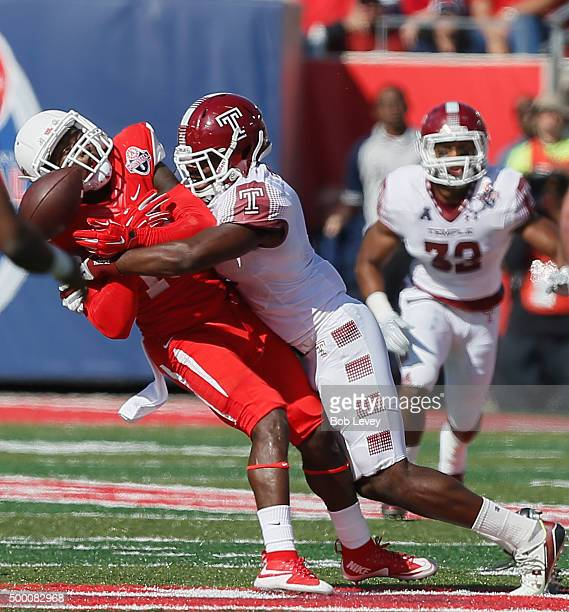 Demarcus Ayers of the Houston Cougars is unable to complete the pass after taking hard hit from Stephaun Marshall of the Temple Owls at TDECU Stadium...
