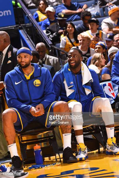 DeMarcus Cousins and Andre Iguodala of the Golden State Warriors smile during a game against the Boston Celtics on March 5 2019 at ORACLE Arena in...