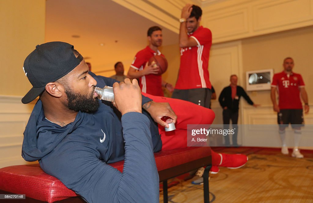 DeMarcus Cousins (L) of Sacramento Kings rests as Xabi Alonso, Javi Martinez and Franck Ribery (2ndL-R) play basketball in an activity session during the AUDI Summer Tour USA 2016 on July 28, 2016 in Chicago, Illinois.