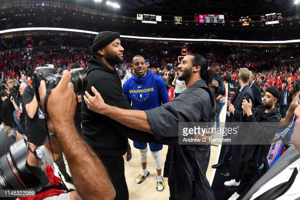 DeMarcus Cousins of the Golden State Warriors and Colin Kaepernick talk after Game Four of the Western Conference Finals against the Portland Trail...