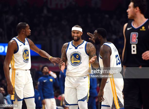 DeMarcus Cousins of the Golden State Warriors is congratulated by Kevin Durant and Draymond Green after scoring a basket against Los Angeles Clippers...