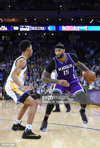 DeMarcus Cousins of the Sacramento Kings dribbles the ball while guarded by Patrick McCaw of the Golden State Warriors during an NBA Basketball game...