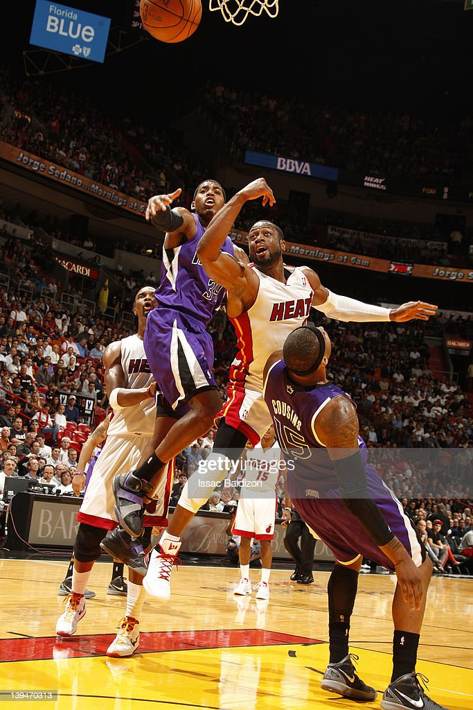 DeMarcus Cousins #15 of the Sacramento Kings falls to the court as Dwyane Wade #3 of the Miami Heat goes to he basket against Jason Thompson #34 of the Sacramento Kings during the game on February 21, 2012 at American Airlines Arena in Miami, Florida.