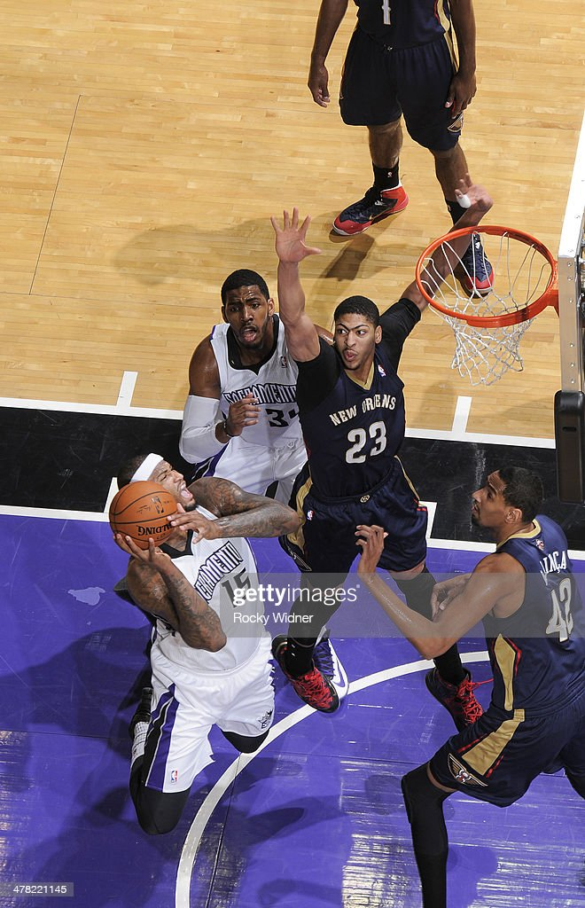 DeMarcus Cousins #15 of the Sacramento Kings goes up for the shot against Anthony Davis #23 and Alexis Ajinca #42 of the New Orleans Pelicans on March 3, 2014 at Sleep Train Arena in Sacramento, California.