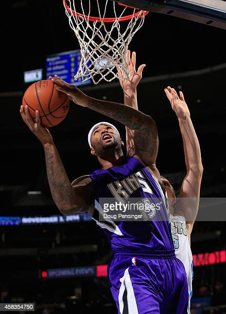 DeMarcus Cousins of the Sacramento Kings lays in a shot against Timofey Mozgov of the Denver Nuggets at Pepsi Center on November 3 2014 in Denver...