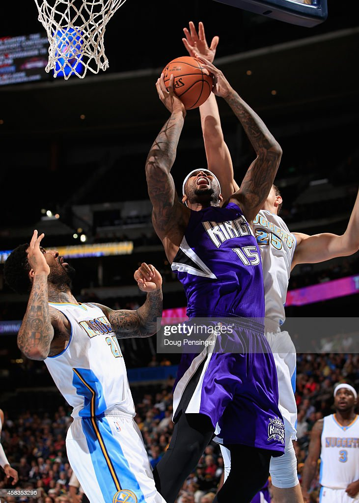 DeMarcus Cousins #15 of the Sacramento Kings takes a shot against Wilson Chandler #21 and Timofey Mozgov #25 of the Denver Nuggets at Pepsi Center on November 3, 2014 in Denver, Colorado.