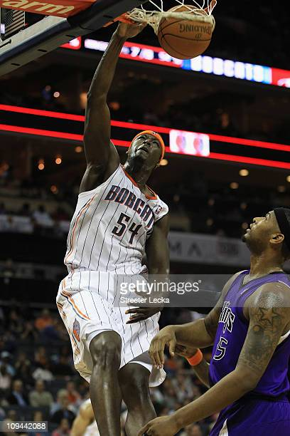 DeMarcus Cousins of the Sacramento Kings watches as Kwame Brown of the Charlotte Bobcats dunks the ball during their game at Time Warner Cable Arena...