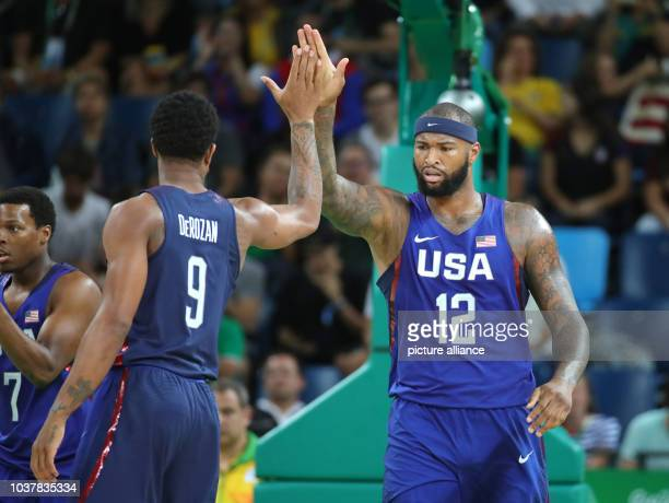 DeMarcus Cousins of the USA gives a high five to teammate Demar DeRozan during the Basketball Men's Gold Medal Game between Serbia and the USA during...