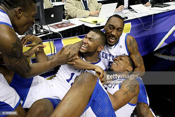 DeMarcus Cousins, Ramon Harris and Darnell Dodson of the Kentucky Wildcats celebrate after Cousins made a 2-point basket at the end of regulation to...