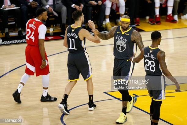 DeMarcus Cousins reacts with Klay Thompson and Alfonzo McKinnie of the Golden State Warriors against the Toronto Raptors in the first half during...