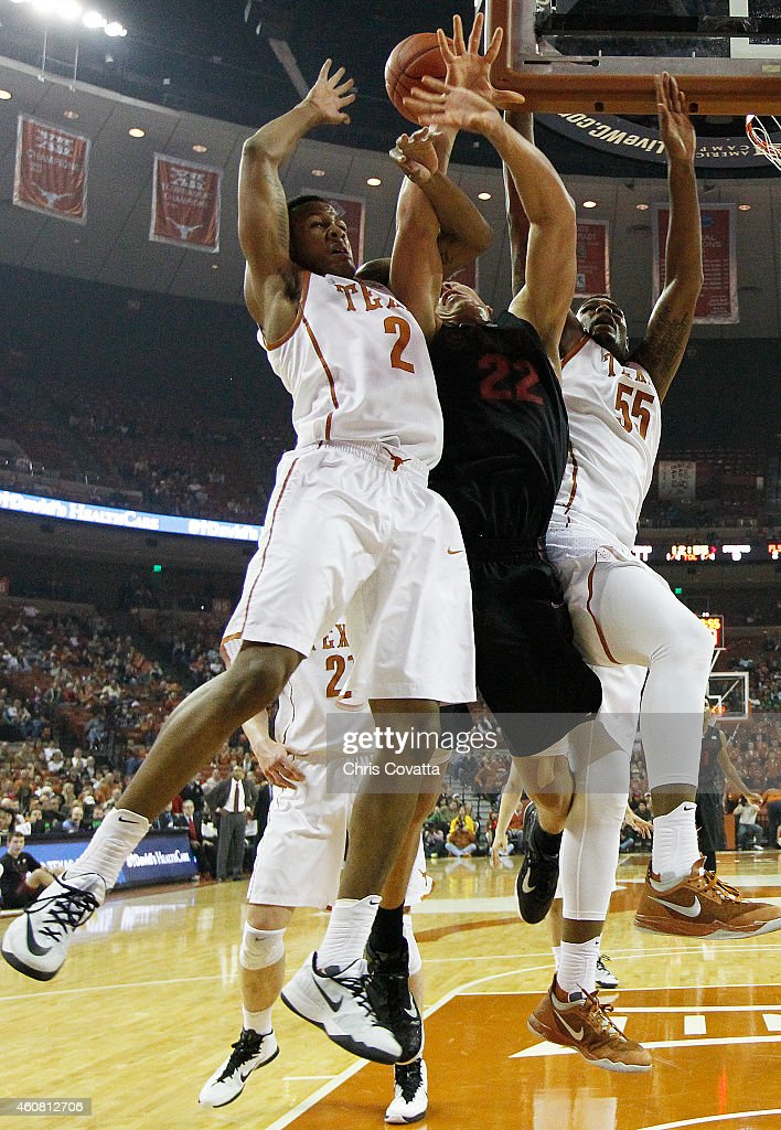 Demarcus Holland #2 and Cameron Ridley #55 of the Texas Longhorns battle Reid Travis #22 of the Stanford Cardinal for a rebound at the Frank Erwin Center on December 23, 2014 in Austin, Texas.