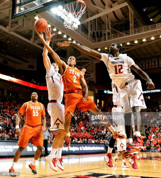 Demarcus Holland of the Texas Longhorns shoots the ball over Dejan Kravic of the Texas Tech Red Raiders and Kader Tapsoba of the Texas Tech Red...