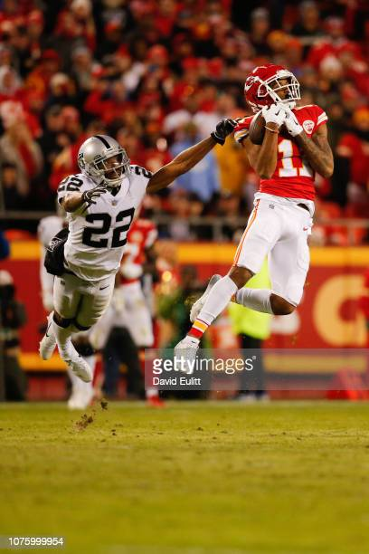 Demarcus Robinson of the Kansas City Chiefs catches the fiftieth touchdown pass of the season for Patrick Mahomes in front of Rashaan Melvin of the...