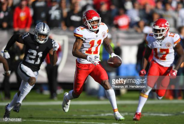 Demarcus Robinson of the Kansas City Chiefs runs with the ball while pursued by Daryl Worley of the Oakland Raiders during the first half of an NFL...
