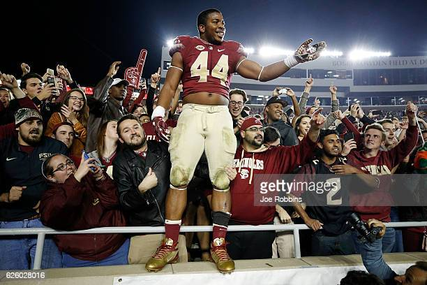 DeMarcus Walker of the Florida State Seminoles celebrates with fans after the game against the Florida Gators at Doak Campbell Stadium on November 26...
