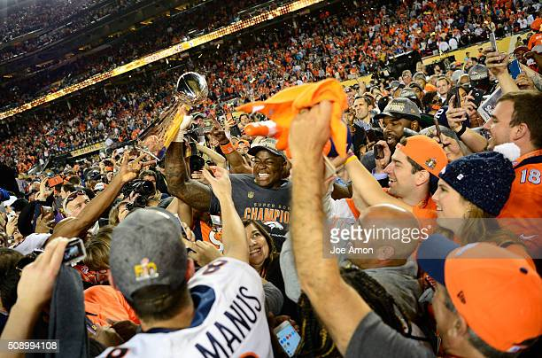 DeMarcus Ware of the Denver Broncos hoists the trophy in a crowd of teammates and family after the game The Denver Broncos played the Carolina...