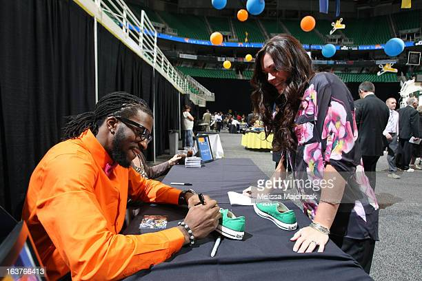 DeMarre Carroll of the Utah Jazz signs an autograph for a fan at the Leapin Leaners and Low Tops Charity Event at Energy Solutions Arena on March 14...