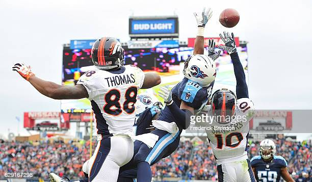 Demaryius Thomas and Emmanuel Sanders of the Denver Broncos fight against LeShaun Sims of the Tennessee Titans to try to make a reception in the end...