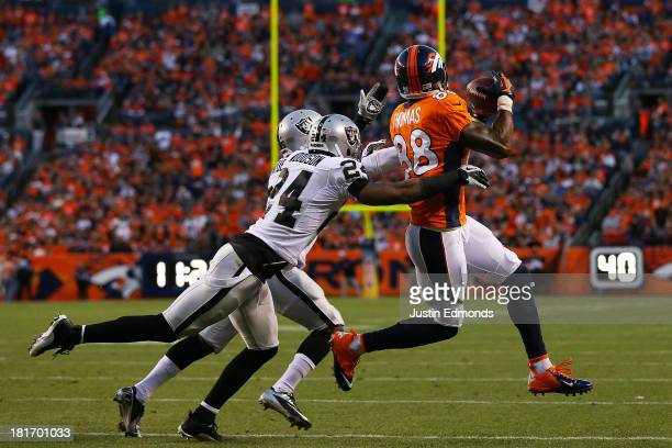Demaryius Thomas of the Denver Broncos completes a 22-yard first down pass reception against the defense of Charles Woodson and DJ Hayden of the...