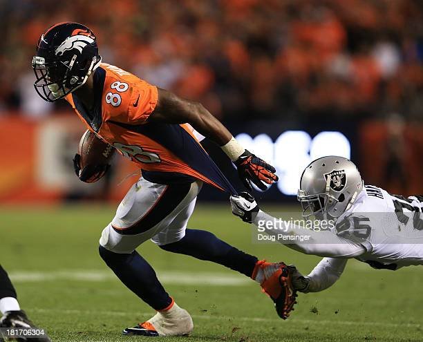 Demaryius Thomas of the Denver Broncos tries to break the tackle of DJ Hayden of the Oakland Raiders at Sports Authority Field at Mile High on...