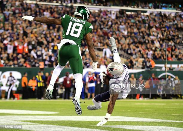 Demaryius Thomas of the New York Jets jumps to receive a catch intercepted by Terrence Brooks of the New England Patriots in the second half of their...