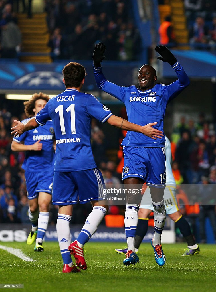 Demba Ba of Chelsea celebrates with teammate Oscar #11 after scoring the opening goal during the UEFA Champions League Group E match between Chelsea and FC Steaua Bucuresti at Stamford Bridge on December 11, 2013 in London, England.