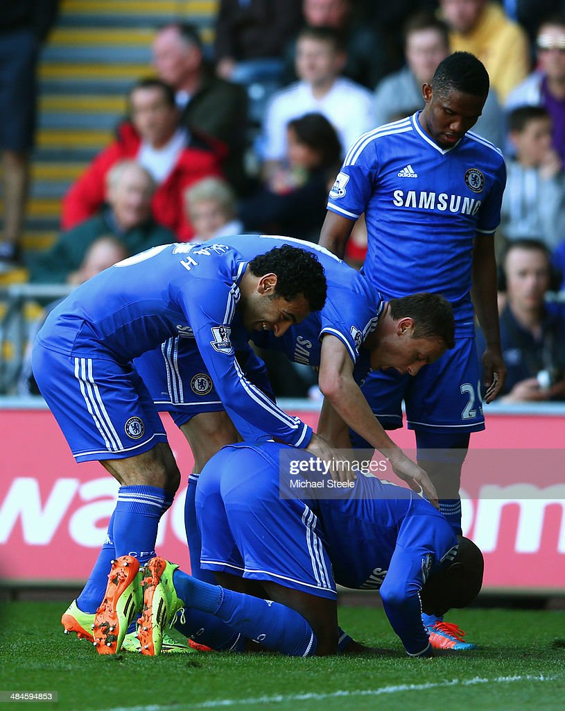 Demba Ba (ground) of Chelsea is congratulated by teammates after scoring the opening goal during the Barclays Premier League match between Swansea City and Chelsea at Liberty Stadium on April 13, 2014 in Swansea, Wales.