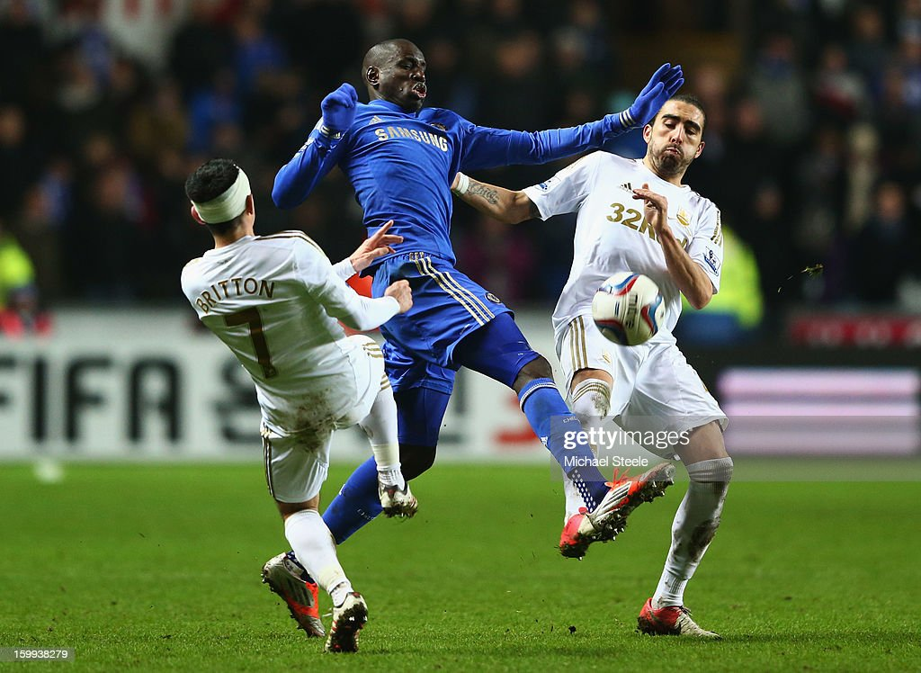 Demba Ba of Chelsea takes on Leon Britton (7) and Chico Flores of Swansea City during the Capital One Cup Semi-Final Second Leg match between Swansea City and Chelsea at Liberty Stadium on January 23, 2013 in Swansea, Wales.