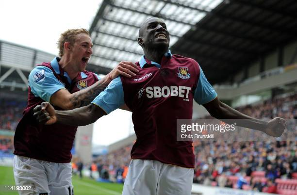 Demba Ba of West Ham United celebrates scoring the openng goal with team mate Jack Collison during the Barclays Premier League match between Wigan...