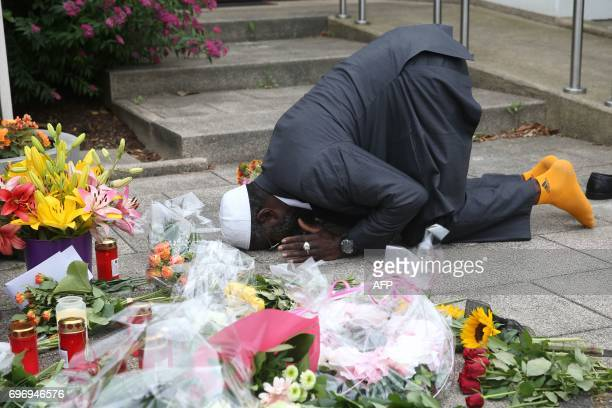 Dembo Kvubally from Gambia prays next to flowers and candles, placed in front of the house of former German Chancellor Helmut Kohl in Oggersheim near...