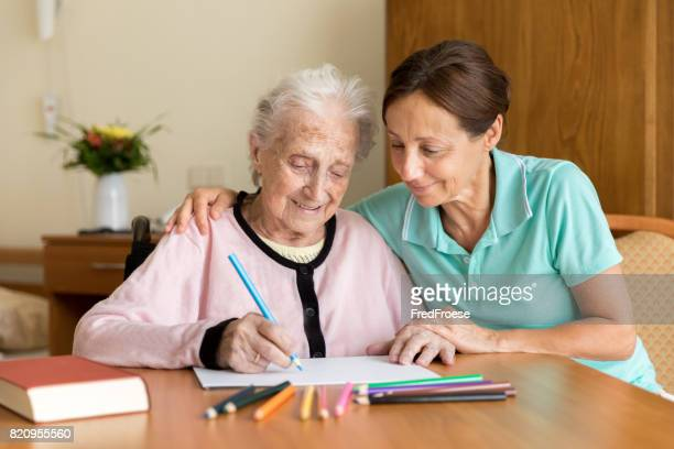 dementia and occupational therapy - home caregiver and senior adult woman - home carer stock photos and pictures