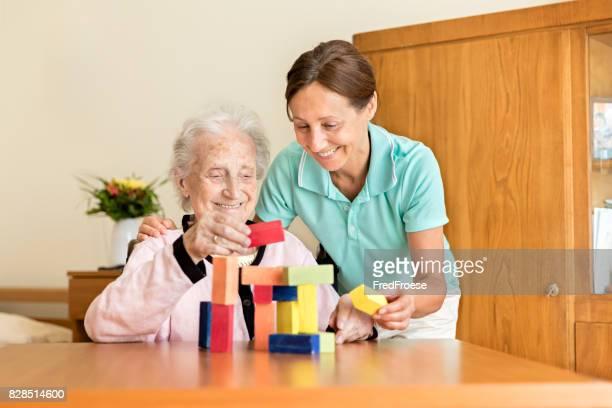 Démence et ergothérapie - maison aux aidants naturels et haute femme adulte, jouer avec des blocs