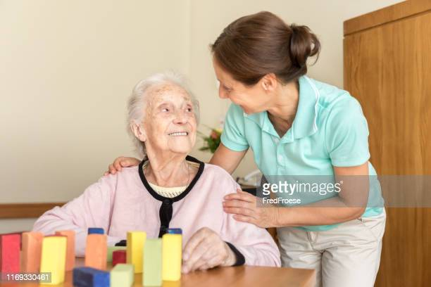 dementia – home caregiver and senior adult woman - alzheimer's disease stock pictures, royalty-free photos & images