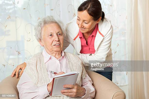 Dementia senior woman with her caregiver at home