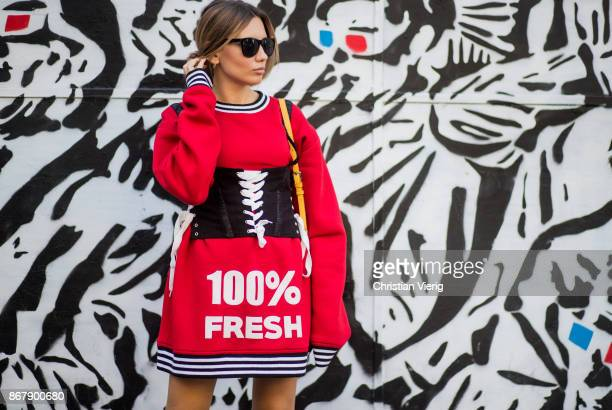 Demet Kamis wearing red sweater worn as a dress with the print 100 percent fresh corset is seen during Tbilisi Fashion Week Spring/Summer 2018 on...