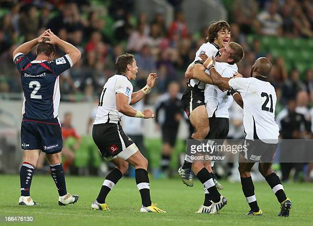 Demetri Catrakilis of the Kings is embraced by his teamates after kicking the winning drop goal during the round nine Super Rugby match between the...