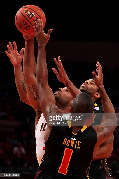 Demetri McCamey of the Illinois Fighting Illini grabs a rebound under pressure from Adrian Bowie of the Maryland Terrapins during the 2k Sports...