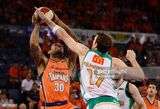 Demetri McCamey of the Taipans is blocked by Peter Crawford of the Crocodiles during the round 17 NBL match between the Cairns Taipans and the...