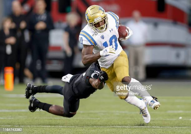 Demetric Felton of the UCLA Bruins breaks off of the tackle attempt by Ja'von Hicks of the Cincinnati Bearcats at Nippert Stadium on August 29, 2019...