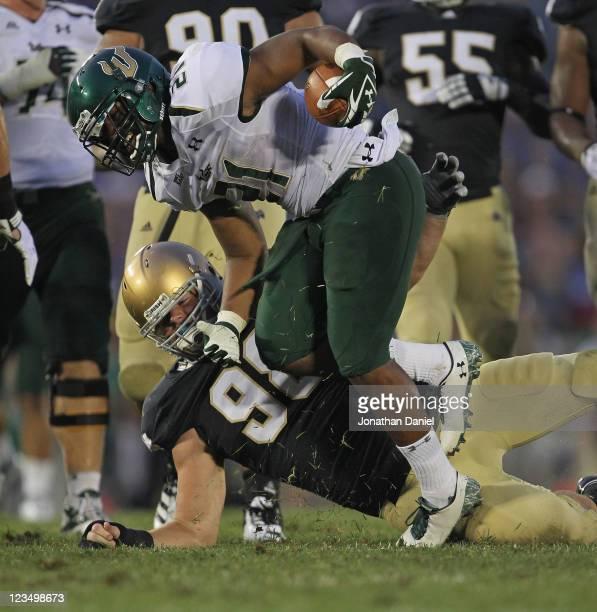 Demetris Murray of the University of South Florida Bulls runs foir yardage as Sean Cwynar of the Notre Dame Fighting Irish tries to pull him down at...