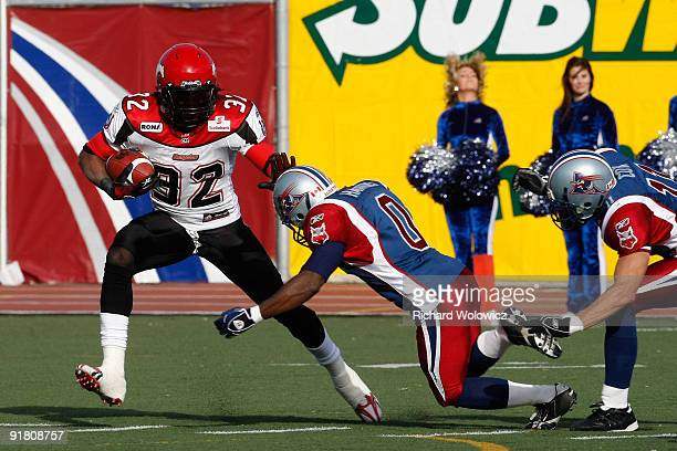 Demetris Summers of the Calgary Stampeders rushes with the ball stiffarming Andrew Hawkins of the Montreal Alouettes during the CFL game at Percival...