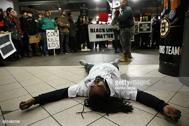 Demetrius Burns lays on the ground while playing the part of Tamir Rice during an interpretive dance at the Black Lives Matter rally at the TD Garden...