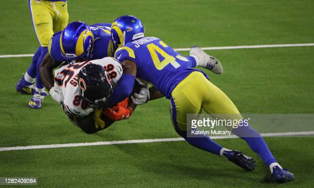 Demetrius Harris of the Chicago Bears is tackled by Kenny Young and John Johnson of the Los Angeles Rams during the third quarter at SoFi Stadium on...