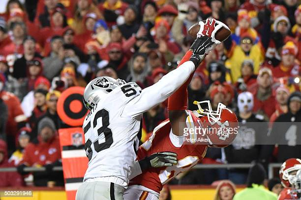 Demetrius Harris of the Kansas City Chiefs catches a touchdown pass over Malcolm Smith of the Oakland Raiders at Arrowhead Stadium during the third...