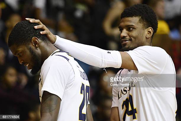 Demetrius Henry playfully congratulates BJ Johnson of the La Salle Explorers as he takes a seat towards the final minutes of the game on the bench...